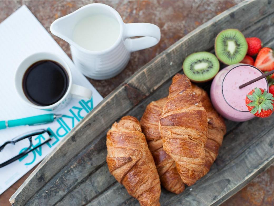 Konferensblock och penna med kaffe, frukt, smoothie och croissanter.