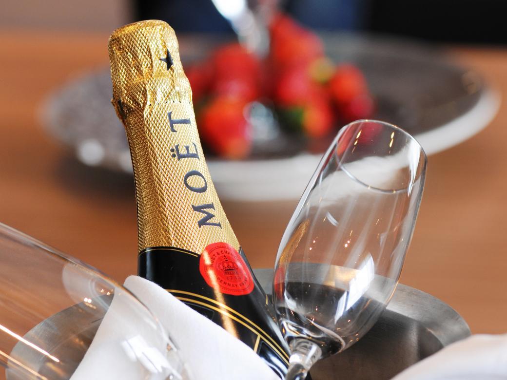 Champagneflaska med två champagneglas och jordgubbar i bakgrunden.