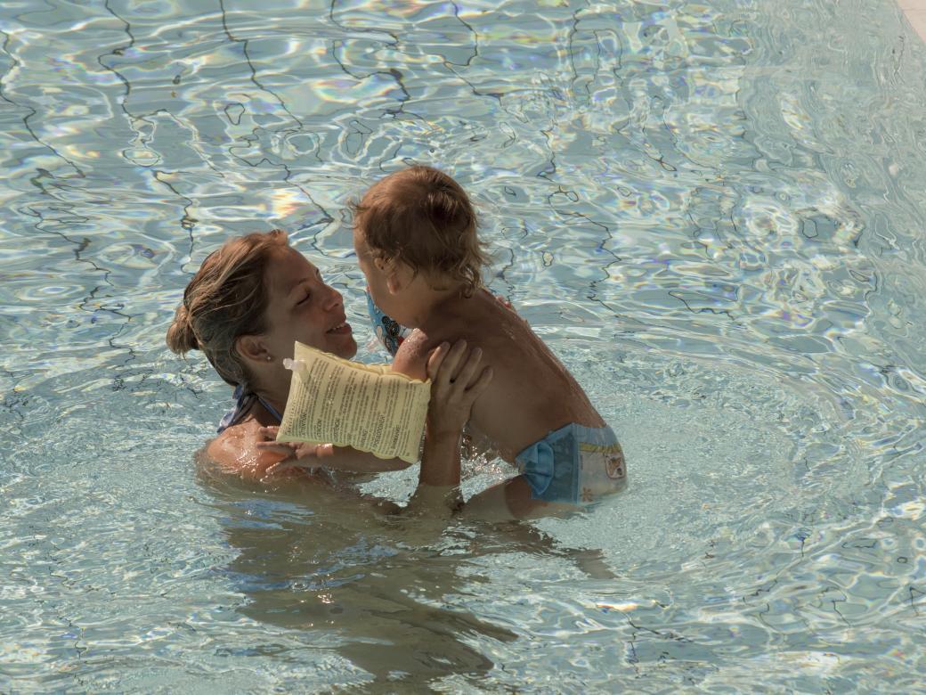 Kvinna och barn badar i poolen