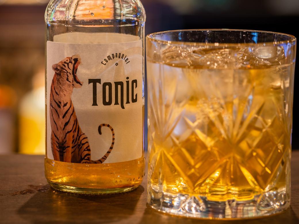 Flaska med Compagniets egen tonic och en drink i whiskeyglas.